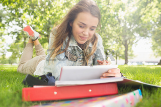 Pretty smiling student lying on the grass studying with her tablet pc