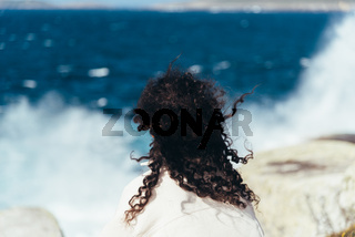 Young woman with curly hair sitting on the rocks looking at the splashing sea. View from behind