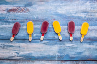 Ice cream stick placed on a blue vintage wooden background