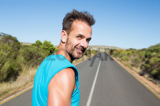 Fit man jogging on the open road smiling at camera