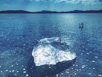 Sharp piece of ice. A symbol of harsh winter. The rays of the sun form rainbow shadows