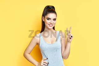 Happy smiling young woman doing victory sign on yellow background