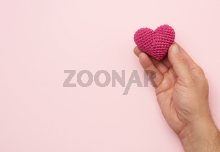 male hand holds red textile heart, pink background