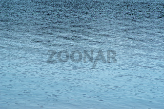 Clear blue water surface with gentle wave patterns