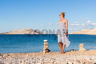 Happy carefree woman enjoying late afternoon walk on white pabbled beach on Pag island, Croatia