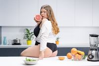 Positive delighted woman sitting on the kitchen table holding a half red grapefruit with lots fruits on the table next to a blander. Sexy overweight girl sitting on the kitchen table