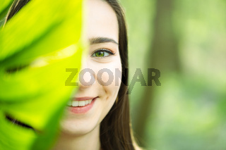 Beauty smiling brunette model with natural make up and green leaves. Copy space. Spa and wellness. Close up