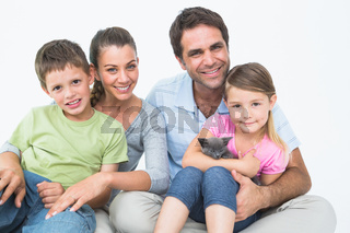 Cute family with pet kitten posing and smiling at camera together