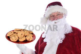 Santa Claus holding a large red platter full of fresh baked chocolate chip cookies, isolated on white.