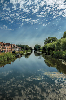 Houses and grove along canal with sky reflected on water in Damme