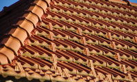 Modern tiled roof in natural red with a blue sky