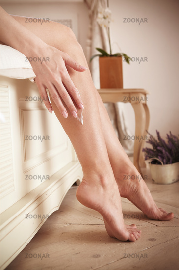 Crop woman smearing cream on legs