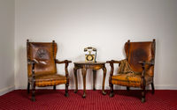 Two wooden armchairs, small coffee table and old telephone set
