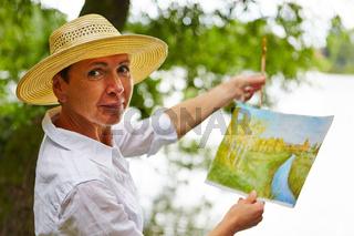 Senioren malt Bild in der Natur
