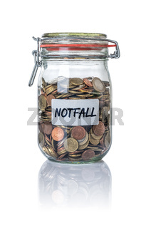 Isolated jar filled with coins labeled Emergency -  Notfall German