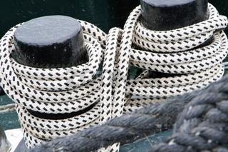 2 Schiffspoller mit festgezurrten schwarz-weiß gestreiften Seilen