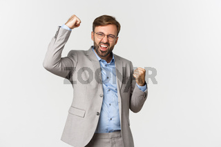 Portrait of successful bearded businessman in grey suit, achieve goal and triumphing, making fist pump gesture and saying yes with confident look, standing over white background