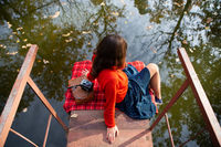 A young woman sits with her back on a bridge near a lake on a sunny day. Plaid, camera, suitcase.