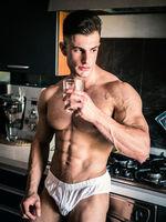 Handsome shirtless bodybuilder drinking water in kitchen