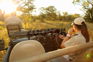 Conservation tracker guide sitting on the front of a safari vehicle
