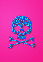 Skull made of blue capsule pills. Pink background