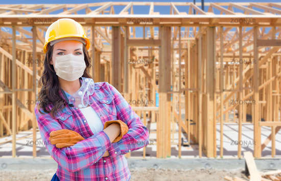 Female Contractor In Hard Hat Wearing Medical Face Mask During Coronavirus Pandemic At Construction Site