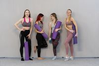 four charming athletic girls in sports out fits talking and smiling standing next to the wall holding a yoga mat, smiling to each other, standing at a grey background