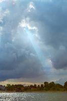 Sun rays shining through dark cloudy sky
