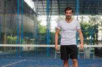 Young handsome Hispanic man at the padel court