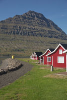 Traditional red painted wooden panel house with mighty Holmatindur mountain in Eskifjordur, Iceland