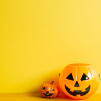 Halloween pumpkins on table with yellow copy space