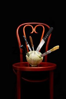 Knives stuck on a white cabbage put on a Thonet chair
