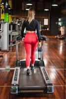 Woman exercising cardio, running workout on treadmill at fitness gym.