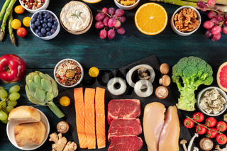 Food design template with copy space. Chief proteins like beef, salmon, chicken and seafood with fruit and vegetables, cheese, nuts and mushrooms, shot from the top