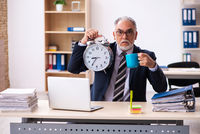 Old businessman drinking coffee in time management concept