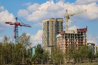 View of construction cranes and houses under construction.