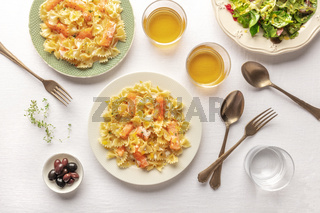 An overhead photo of a plate of salmon pasta, Farfalle with smoked salmon and cream sauce, shot from the top with wine