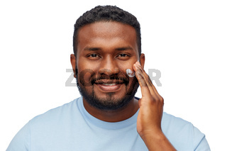 african american man applying moisturizer to face