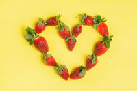 Strawberry heart on a yellow background. Fresh strawberries closeup. Valentine's day, strawberry day concept.
