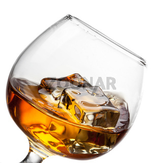 Splash of whiskey with ice in glass isolated on white background