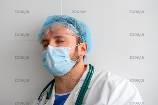 Exhausted doctor with closed eyes in face mask