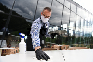 Waiter cleaning the table with Disinfectant Spray in a restaurant
