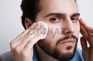 Bearded man with the help of a hygienic cotton pad is cleaning his face skin.