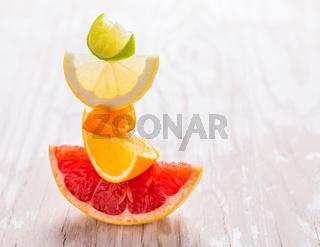 Slices of citrus fruits on wooden background. Preparing lemonade