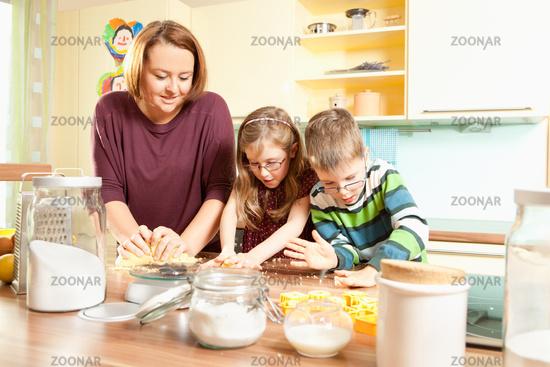 Mother baking cookies with her children