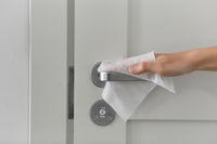 hand cleaning door handle with antiseptic wet wipe