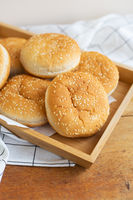 Freshly baked lush burger buns lie on a wooden tray on a table with a white napkin. Top view, close-up. Yellow flavored pastries with white sesame seeds.