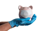 Doctor or Nurse Wearing Surgical Gloves Holding Piggy Bank Wearing Medical Face Mask Isolated on White