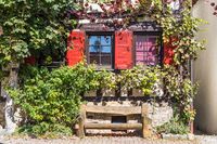 Rustic wooden bench in front of half-timbered facade under window with red shutters