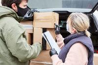 Paketdienst kontrolliert Lieferschein von Paketen